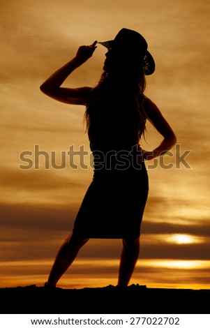 A silhouette of a woman in her dress with her western hat. - stock photo
