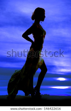 A silhouette of a woman in her formal dress looking to the side. - stock photo