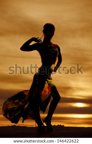 a silhouette of a woman in her long flowing dress with her arm up. - stock photo