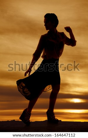 A silhouette of a woman in her sheer skirt looking over her shoulder. - stock photo