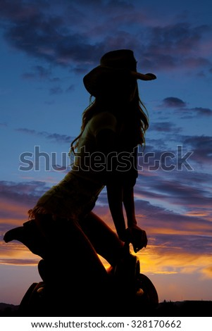 A silhouette of a woman in her western hat, kneeling on her saddle in the outdoors - stock photo