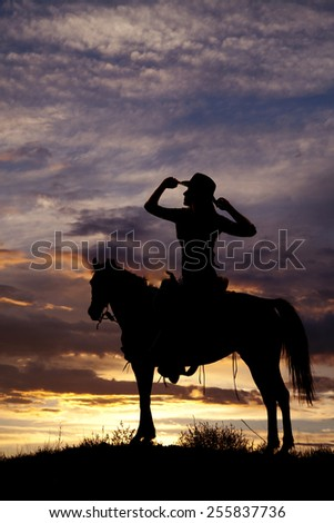 A silhouette of a woman in the outdoors sitting on her horse. - stock photo