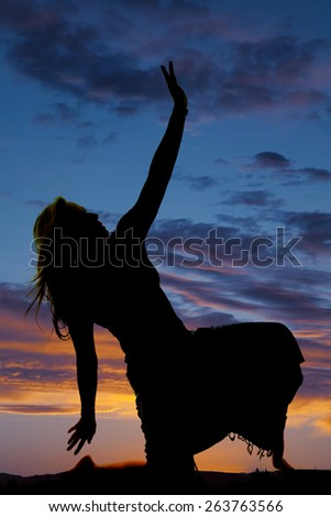 A silhouette of a woman kneeling in her skirt posing. - stock photo