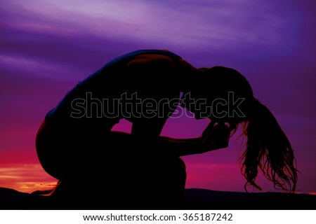 A silhouette of a woman leaning into a ball with her hair flipped over. - stock photo