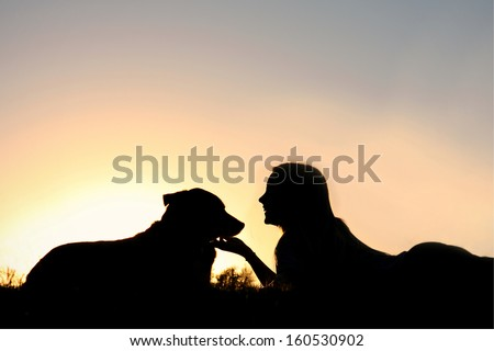 a silhouette of a woman lying on her stomach in the grass smiling and lovingly petting her German Shepherd dog. - stock photo