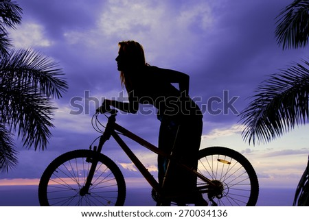 a silhouette of a woman on her bike looking at something. - stock photo