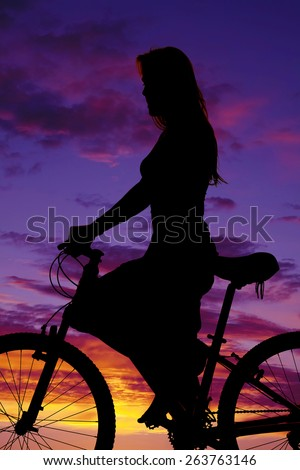 a silhouette of a woman on her bike, riding for the pleasure of it. - stock photo