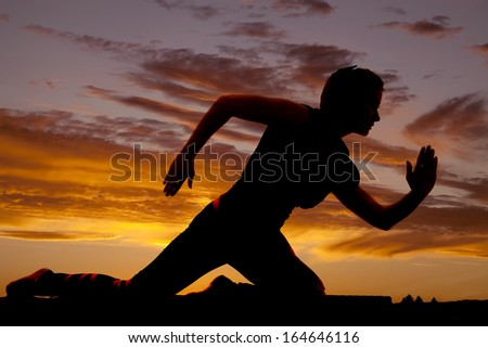 A silhouette of a woman on her knees in a running position. - stock photo