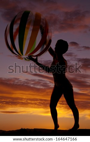 A silhouette of a woman playing with a beach ball. - stock photo