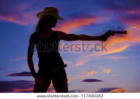 a silhouette of a woman pointing her pistol at something. - stock photo