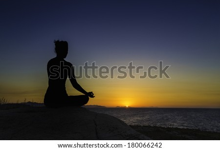 A silhouette of a woman practicing yoga in the lotus position in a sunset. - stock photo