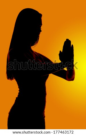 a silhouette of a woman praying in reverence - stock photo