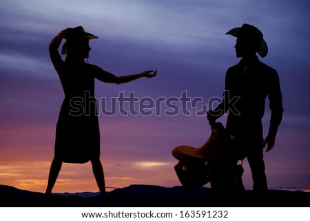 a silhouette of a woman reaching out her hand to the cowboy in the picture. - stock photo