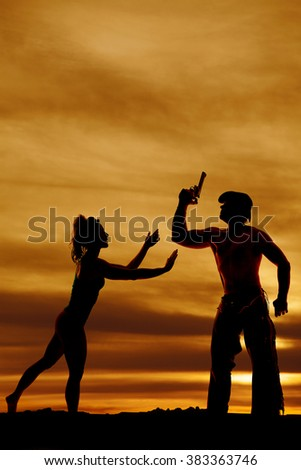 a silhouette of a woman reaching out to her cowboy that is holding his pistol. - stock photo