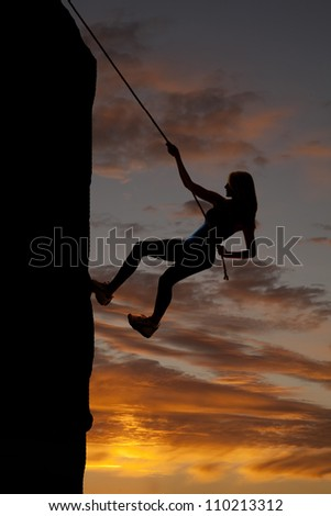 A silhouette of a woman rock climbing with a beautiful sky behind her. - stock photo