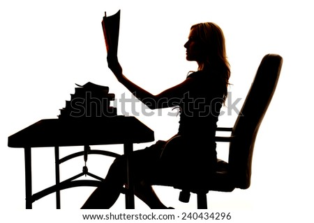 a silhouette of a woman sitting at a desk, reading a book. - stock photo