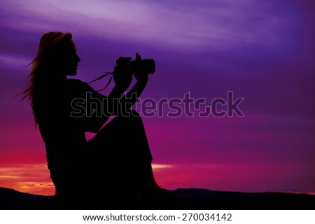 A silhouette of a woman sitting holding on to her camera with a beautiful sunset. - stock photo