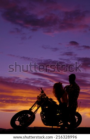 A silhouette of a woman sitting on a motorbike leaning back while her man holds her. - stock photo