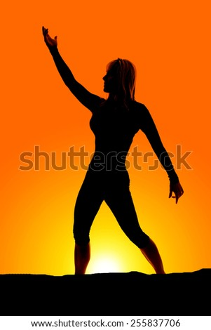 A silhouette of a woman standing and stretching. - stock photo