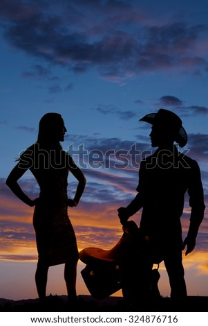 a silhouette of a woman standing next to her cowboy. - stock photo