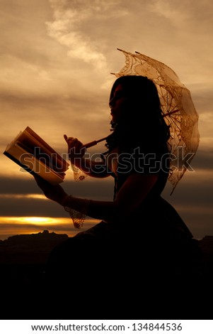 A silhouette of a woman using the last light of day to read a book out in the sunset. - stock photo