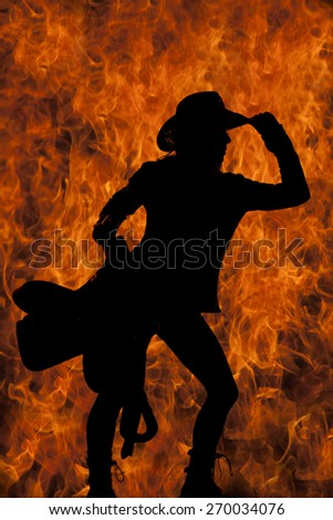 A silhouette of a woman with a fire background touching the brim of her hat, and a saddle on her hip. - stock photo