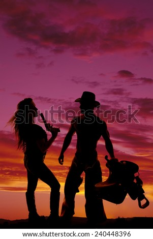 A silhouette of a woman with a gun standing next to her cowboy. - stock photo