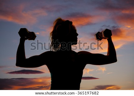 a silhouette of a woman with fit arms working out with weights. - stock photo