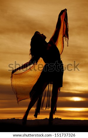 a silhouette of a  woman with her sarong holding it up and dancing. - stock photo