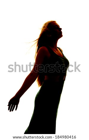 A silhouette of a woman with the wind blowing her hair and her arms back. - stock photo