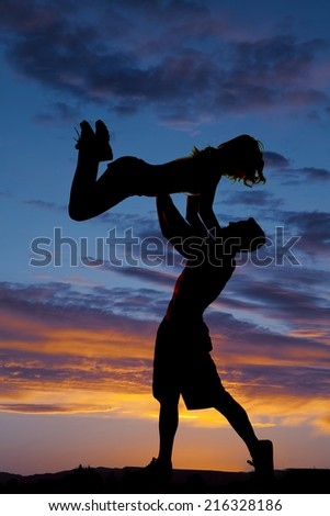 A silhouette of a woman woman being lifted up by her man in the outdoors. - stock photo