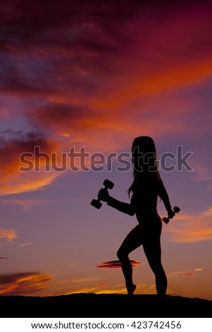 a silhouette of a woman working out with weights, in the outdoors. - stock photo