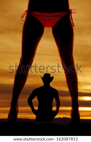 A silhouette of a womans legs in a bikini with a cowboy in the back. - stock photo
