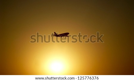 A silhouette of an airplane on a background of gold sunset.