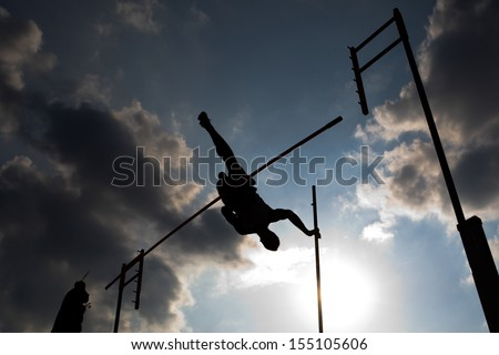 A silhouette of athlete during pole vault - stock photo