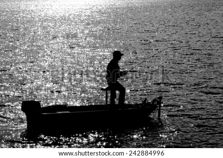 A Silhouette of Fisherman on Fishing boat patiently waiting for the fish to catch a bait in a hot sunny day at noon - stock photo