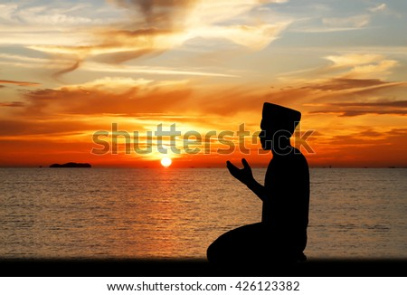 A silhouette of islamic praying at sunset.