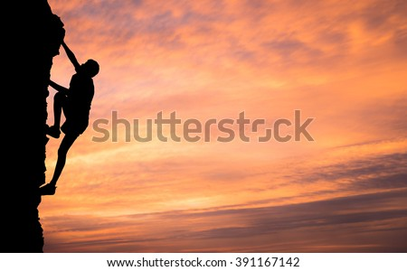 A silhouette of man climbing on stone, mountain at sunset. - stock photo