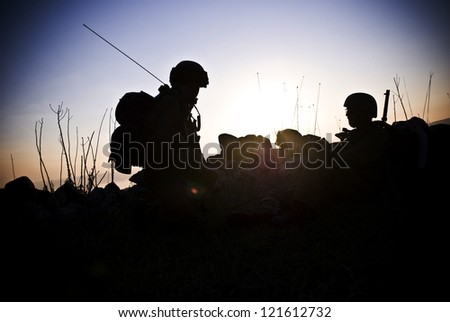 A silhouette of the military person on a background of a sunset - stock photo
