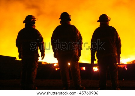 A silhouette of three Fire Fighters watching a fire - stock photo