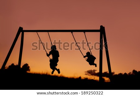 A silhouette of two children swinging outside at sunset.