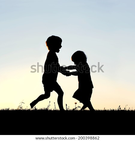 A silhouette of two happy little children, a young boy and his baby brother, holding hands and dancing and playing in front of a sunset in the sky. - stock photo