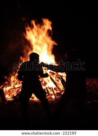 A Silhouette of Two Men in Front of a Fire