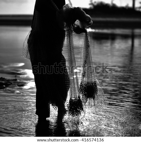 A silhouette of unknown traditional Fishermen hold the fishing nets at a beach in black and white - stock photo