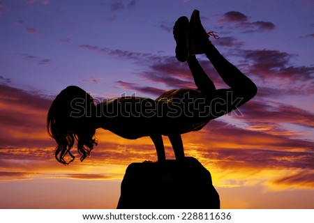 A silhouette of  woman doing a yoga strength pose on a rock.