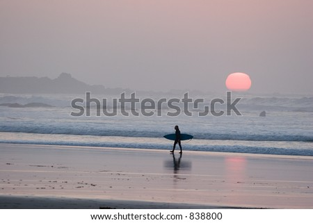 A silhouetted surfer leaves the water at sunset - stock photo