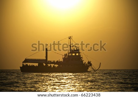 a silhoutte of a ship at sunset - stock photo