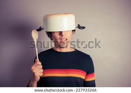 A silly young man is wearing a cooking pot on his had and is holding a wooden spoon - stock photo