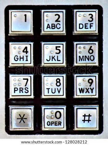 A silver and black keypad on a public payphone - stock photo