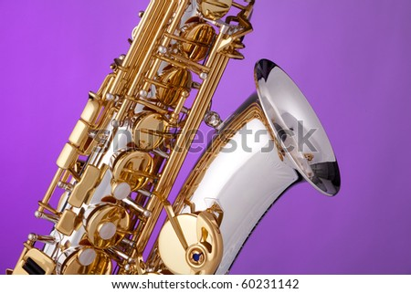 A silver and gold professional alt saxophone isolated against a pink background. - stock photo